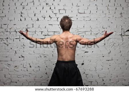 Strong muscular man back at  white wall background in flying and free standing