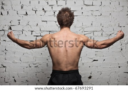Strong muscular man back at white wall background in hard rage standing - stock photo