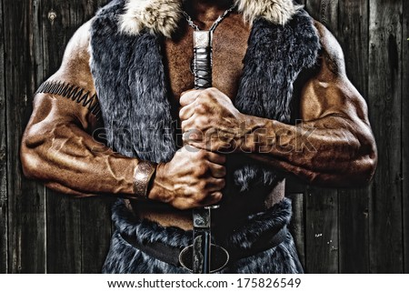 Strong muscular man defender warrior with sword in hand on background of old wooden planks - stock photo