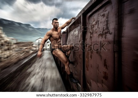 Strong muscular man hanging on moving train