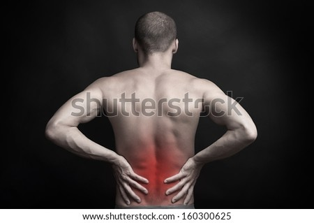 strong muscular man holding his aching back with hands - spine ache concept - stock photo