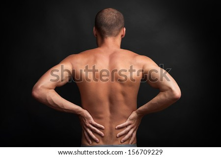 strong muscular man holding his naked back with hands - spine ache concept - stock photo