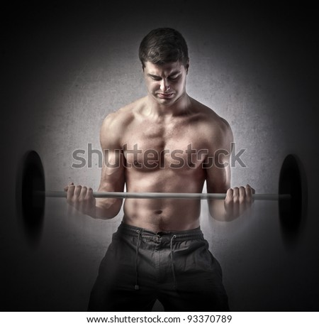 Strong muscular man lifting weights - stock photo