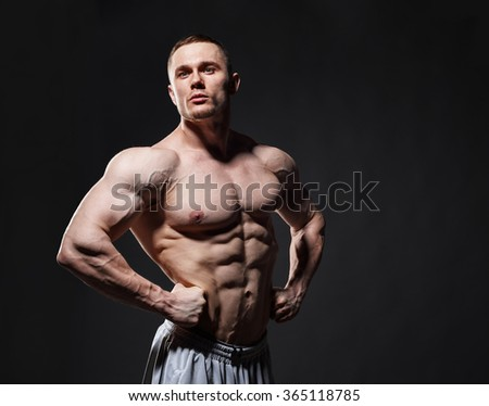 Strong muscular man posing in studio over dark background. Model looking at the side