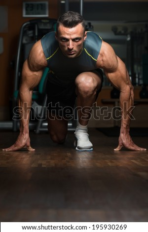 Strong Muscular Men Kneeling On The Floor - Almost Like Sprinter Starting Position - stock photo