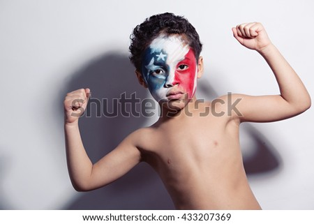 Strong Patriot.  Portrait of a young, mixed race boy wearing red, white, and blue face paint and showing his muscles.   - stock photo