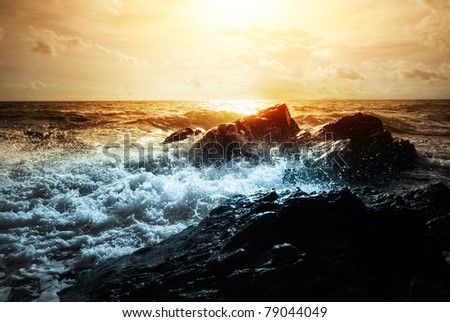 Strong sea waves breaking on coast rocks with splashes - stock photo