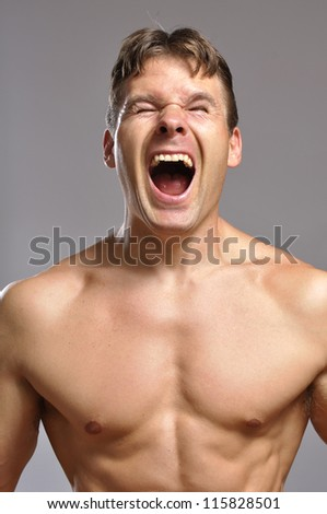 Strong shirtless man screams while he flexes muscles - stock photo