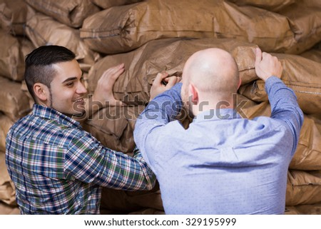 Strong smiling american workmen unloading shed with coal bags 