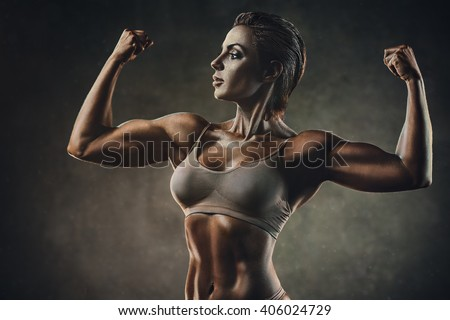 Strong sports woman on wall background. Film style colors effect. - stock photo