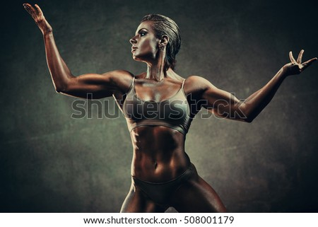 Strong sports woman on wall background. Vintage film style colors effect.