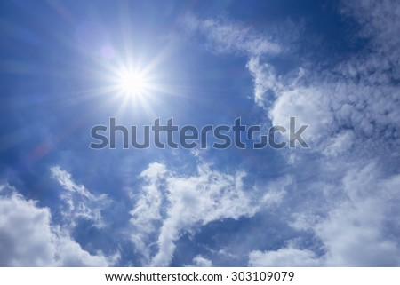 Strong sun in blue sky and white clouds - stock photo