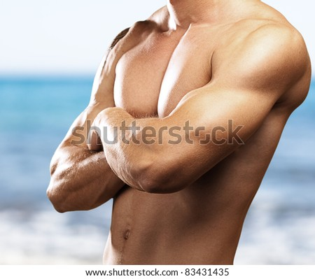 strong torso of young man against a sea background - stock photo