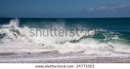 Strong waves breaking onto the sandy beach on north shore of Kauai