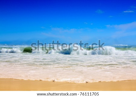 Strong waves crash over the beach - stock photo
