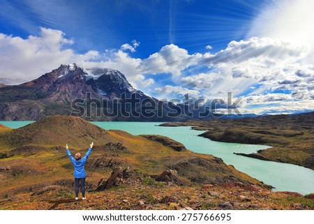 Strong winds in the Chilean Patagonia. National Park Torres del Paine, Lake Pehoe. The woman raised her hands with delight the beauty of nature - stock photo