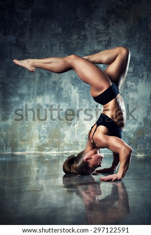 Strong woman bodybuilder standing upside down on wall background. - stock photo