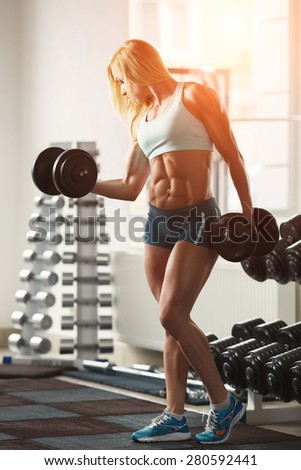 Strong woman bodybuilder with white hair and tanned body pumps up the muscles lifting dumbbells in the gym. Sports and fitness. Fitness woman in the gym. Fitness woman with dumbbell. - stock photo