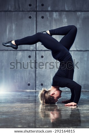 Strong woman gymnast in black clothing stretching upside down on wall background. - stock photo