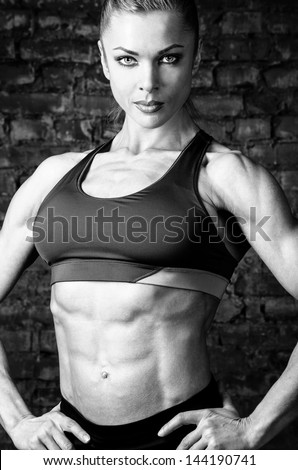 strong woman is posing against brick wall - stock photo
