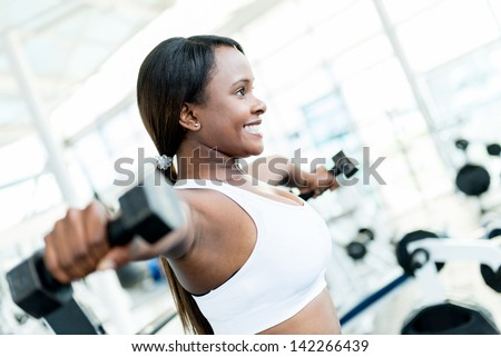 Strong woman weightlifting at the gym working out - stock photo
