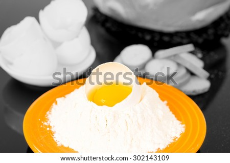 Strong yellow colored plate with flour crater containing cracked egg, black and white sorroundings shot from above side angle.