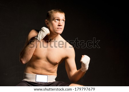 Strong young boxer seeking inspiration as he raises his eyes to the ceiling during a practice or fight while standing with his fists raised on a dark background with copyspace - stock photo