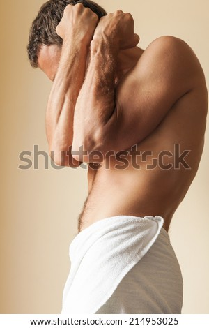 Strong young Caucasian man hides behind his blocking hands - stock photo