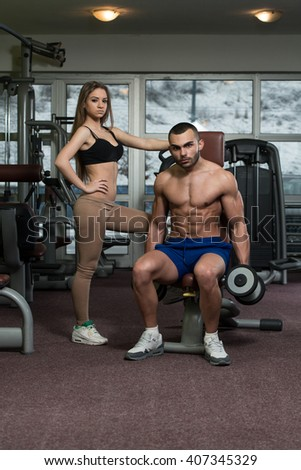 Strong Young Couple Working Out With Dumbbells For Biceps In The Gym With Exercise Equipment - stock photo