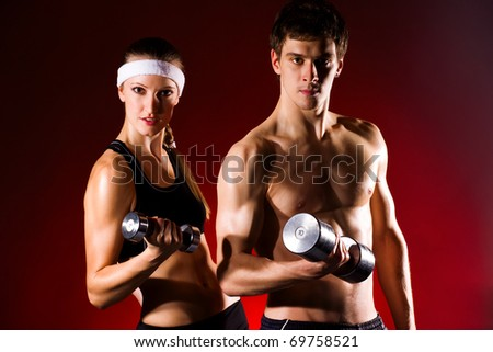 strong young couple working out with dumbbells. Shot in studio on a red background.