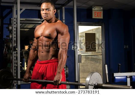 Strong young male exercising with his shirt off. Mean stare into the camera. plenty of room for advertising.  - stock photo