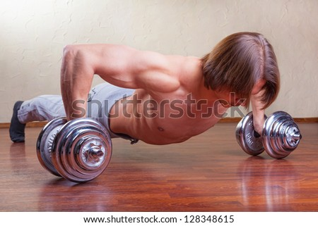 Strong young man doing push ups in his home - stock photo