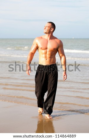 Strong young man portrait at the beach - stock photo
