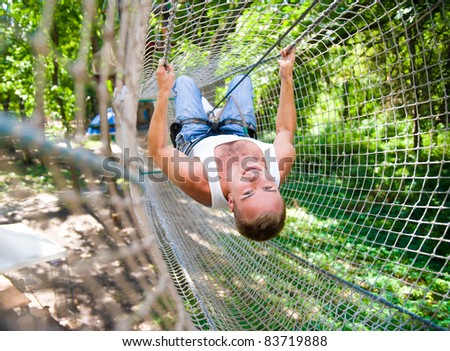 strong young men in a rope park on the wood background - stock photo