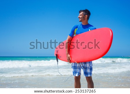 Strong young surf man at the beach with a surfboard. - stock photo