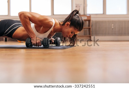 Strong young woman doing push-ups on dumbbells in gym. Fit female exercising in health club with copy space. - stock photo