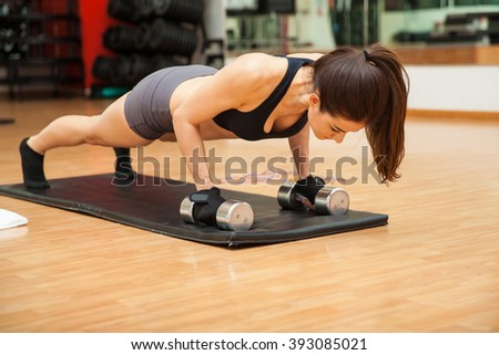 Strong young woman in sporty outfit doing some push ups at the gym as part of her workout - stock photo