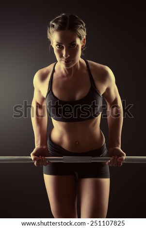 Strong young woman with beautiful athletic body doing exercises with barbell. Fitness, bodybuilding. Health care. - stock photo