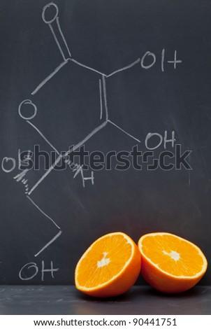 Structural formula of vitamin C on blackboard with orange - stock photo
