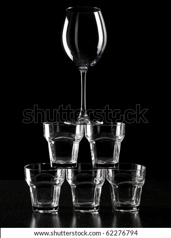 Structure like a pyramid from different glasses and wineglass on top - stock photo