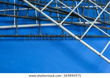 Structure of more metal wire net cross each other over blue texture - stock photo