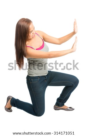 Struggling Asian woman in casual clothes, kneeling with extended arms, defending, forcing, pushing, fighting against imaginary insert object encroaching from side