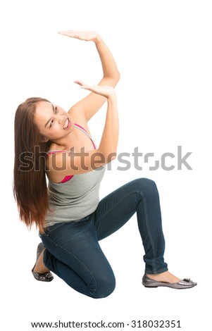 Struggling Asian woman kneeling under weight in casual clothes, arms extended supporting, getting crushed, pushing up against falling product placement from above. Isolated on white background - stock photo