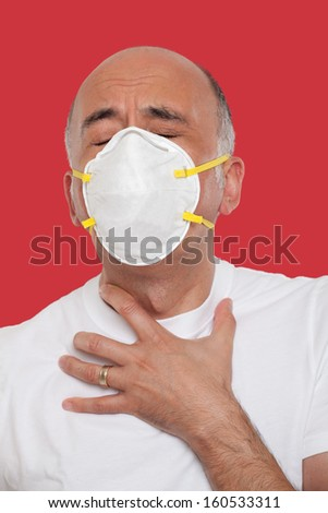 Struggling man wearing a mask protection  - stock photo