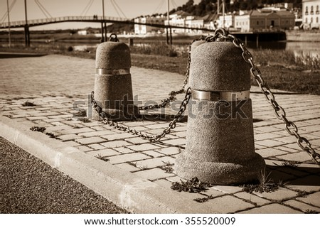 Stub posts linked in a chain on a quay in a small Portugal town - stock photo