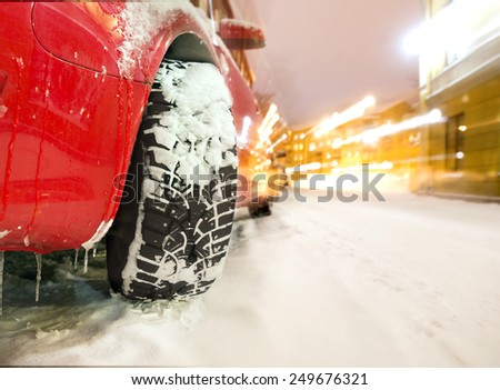 Studded tyre of red car on street in winter evening - stock photo