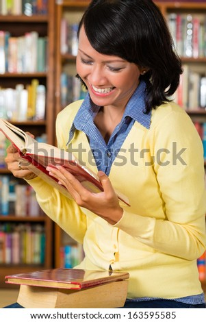 Student - a young Asian woman or girl learning in a library reading a book - stock photo