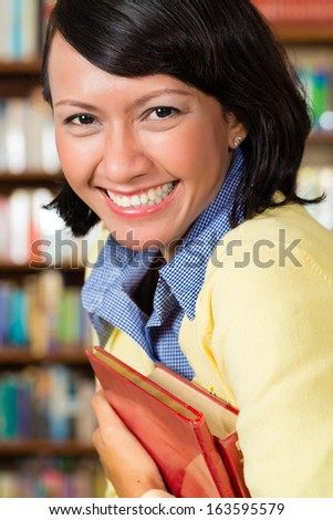 Student - a young Asian woman or girl learning in a library, she proudly holds a book or textbook - stock photo