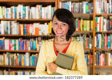 Student - a young woman or girl learning in a library, she proudly holds a couple of books and smiling - stock photo