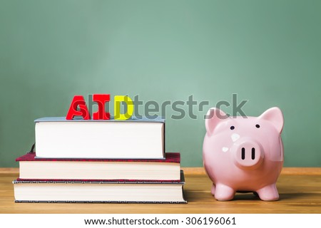 Student aid theme with textbooks and piggy bank and chalkboard background - stock photo